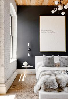 White brick wall, black wall, wood ceiling, white light fixture, white bedding, fur throw blanket, black and white graphic pillows, simple white artwork, and beige rug