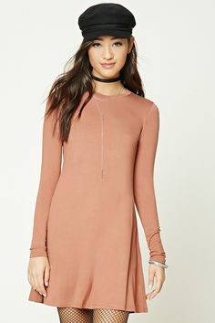 A textured knit swing dress featuring a crew neckline and long sleeves.