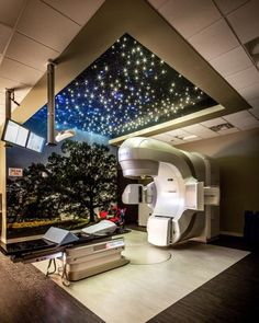 State of the art LINAC room features an evening view of the fiber optic star ceiling and graphic of a local beloved tree. Photo: ©2015 Derrick Simpson / McMillan Pazdan Smith ©2015