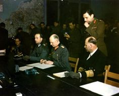 German military commander Generaloberst (Colonel General ) Alfred Jodl (1890 - 1946) (center) signs the German Instrument of Surrender, Reims, France, May 7, 1945. Seated on his right is Major Wilhelm Oxenius (1912 - 1979) and Admiral Hans-Georg von Friedeburg (1895 - 1945) is on his left (in the dark uniform). (Photo by PhotoQuest/Getty Images