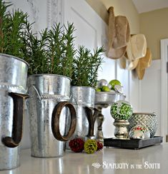 Hobby Lobby letters hot glued onto buckets with rosemary clippings (smells good if you have a fake Christmas tree)