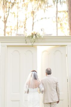 Bride with father walking down the aisle huge wedding doors  | Amy and Mikes Lakeside wedding | www.AmalieOrrangePhotography.com