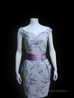 Vestido en tafetán gris bordado al tono con escote corazón. Fajín maquillaje marcando cintura.