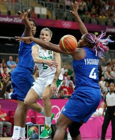 Brazil guard Karla Costa, center, dumps off the ball as she is pressured by France's Endene Miyem, left, and Isabelle Yacoubou during a basketball game at the 2012 Summer Olympics, Saturday, July 28, 2012, in London. (AP Photo/Charles Krupa)