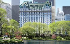 The castle-like exterior of the Plaza, located a half-block from Central Park, as seen across the tree-lined Pond in New York City.