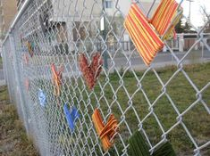 Yarn hearts on chain link fence
