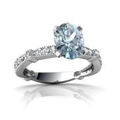 14K White Gold Oval Cut Aquamarine Engagement Ring - This gorgeous 14K White Gold Oval Cut Aquamarine Engagement Ring has a lovely curvy band which fits perfectly with the matching wedding band. It features a 8X6mm Oval-Cut Aquamarine center stone surrounded by 24 diamonds. The total gem weight for the ring is 1.8 carats set in solid 14k White Gold. The band is 1/8 of an inch at its widest point down to 1/16 of an inch at the back & is 1/4 of an inch high off the finger…