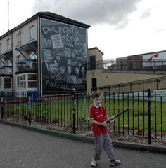 Bloody Sunday Bogside - ... totes a toy gun in front of one of the Bogside Murals in Derry, Northern Ireland, which commemorate the Bogside Massacre, better known as Bloody Sunday.
