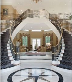 The inlaid marble invites you into a magnificent entrance which features a stunning curved double staircase.Interior Design by C. Taylor Interiors.