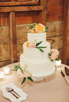 A three-tiered white wedding cake decorated with garden roses, ranunculus, and greenery, created by Grandma Miller's Pies and Pastries.