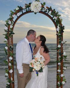 Beach wedding arch - trellis with white flowers at a beach wedding ceremony in Panama City Beach