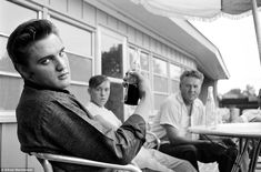 Elvis Presley relaxes with a Pepsi on the porch of his home at 1034 Audobon Drive, Memphis, Tennessee, on July 4, 1956