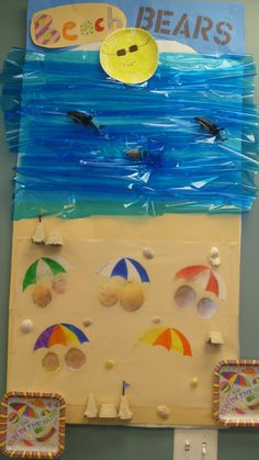 Childcare/Preschool Bulletin Boards: summer at the beach. blue cellophane stapled to make waves, rubber dolphins jumping out of water, pipe cleaners help fasten dolphins to board. Sand is contact paper covered in real sand for texture. real shells hanging on nails, sand castles made of egg cartons rolled in glue covered in sand, I took close up pictures of children wearing sunglasses. umbrellas made out of paper.