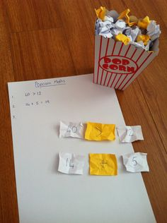 """On the white paper (plain popcorn) I wrote numbers, on the yellow (buttered popcorn) I wrote math symbols (+ – x ). Students can then choose 2 pieces of white popcorn and 1 piece of yellow. They write the equation and answer in their books."""