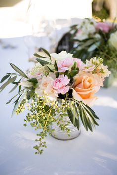 Centerpiece idea - up cycle tin cans, some peachy roses and I really like those little blueish-green ball things