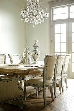 wonderful juxtaposition of materials...rustic table, silver chairs, natural fabric, nailheads on upholstery, wood floor, fancy chandelier, simple accessories...love it!