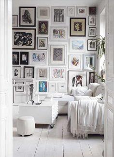 På en vägg i vardagsrummet sitter tavlor som nära och kära har målat, en unik samling som ger mycket karaktär. Soffbordet är en vitmålad gammal ritningshurts som försetts med hjul.