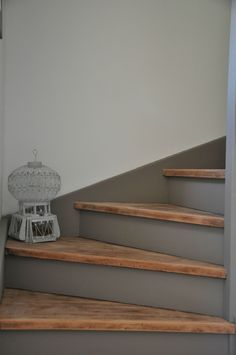 Stair treads left bare wood, waxed, risers painted in stormy grey, clean line on the wall.