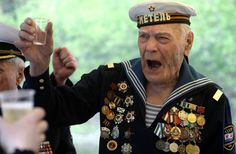 A Russian World War II veteran wearing a Navy uniform (no name given) toasts his fellow veterans during the annual Victory Day celebration in downtown Moscow on Saturday, May 9, 2009