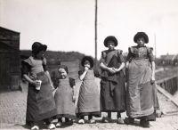 Streekdracht  Unisex kleding in 1927  Bunschoten-Spakenburger dracht   In Bunschoten-Spakenburg warenjongens en meisjes in de leeftijd van één tot vier jaar hetzelfde gekleed.Ze droegen een jurkje met een geruit schort. Alleen aan het katoenen mutsje, de klapmuts,was te ziendat het kind een jongetje was. Het tweede kind van links op de foto is dus een jongen. Een meisje had een satijnen muts met een dikke rand vanwol op, de pluummuts.   Na het vierde jaar kreeg een jongen een miniatuur…