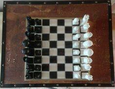 « Jeu d'échecs » (Média mixtes),  60x60x32 cm par Riquet Pièces en résine sur plateau en céramiques posé sur caisson bois recouvert d'une feuille de cuivre .