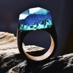 Formed from wood, resin, and beeswax, Canadian jeweler Secret Wood forms tiny worlds within the space of a finger. These environments contain everything from snowcapped mountains to deep blue lagoons, appearing like tiny snow globes atop one's hand. Like a gemstone, each ring has an angular surface,