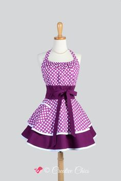 Put a little flirty flair in your kitchen cooking and everyone who sees you! The flirty chic pinup apron features a two-layered skirt in a berry purple and white dot for the bodice. A full ruffled skirt and an extra-wide lined waistband that is a flattering style on women of all shapes and sizes. Bodice top features elastic bodice top that provides good coverage and fit for all bust sizes. Long waist ties offer the option of tying in front or in back. Care Instructions: Machine Washable…