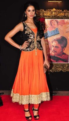 #Desi #FW13: Nargis Fakhri wears an embroidered waist coat in black with gold zari work over orange Anarkali with golden borders