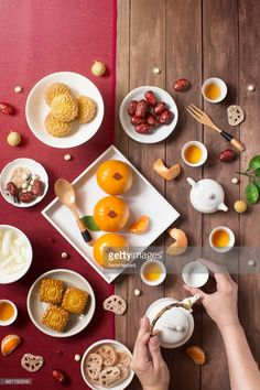 Flat lay Chinese new year food and drink on wooden table top still life. Hand serving tea. Text appear in image: Prosperity & spring.
