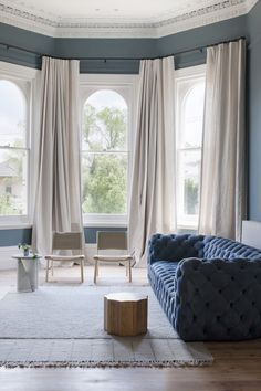 A Paola Navone Chester Moon Sofa in blue anchors the living room. Off-white linen curtains add privacy to the street-facing front room.