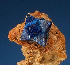 Tiny but super-rare, this cumengeite crystal perches on a throne of brecca, or broken-up rock and mineral naturally cemented together. Cumengeite is closely related to boleite, which forms cubes of a similar blue hue and is found in lead and copper deposits. This cumengeite measures just a centimeter across and comes from Mexico.