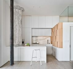 The careful coordination of color continues in the kitchen, where the gray and white marble backsplash, lit with faint orange lights, mediates between the ashen column and ochre cabinets.
