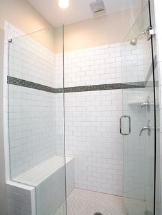 This walk in shower features white subway tile with glass tile accent strip and penny style tile floor, wall mount shower head along with overhead rain shower head, frameless glass door and a built-in bench.