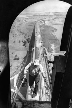 """June 6, 1953: The 363-foot towers of the Bronx-Whitestone Bridge got their first coat of paint in six years. The painters could work only in the daytime, during dry weather with low winds. """"One distraction they don't have: no one will poke a finger at the paint to see if it's really fresh,"""" the caption read. Photo: Ernie Sisto/The New York Times"""