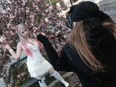 Shadow Self wearing white, posing under a pink tree while Henry Söderlund is taking picture. Maria Maunula is behind the bts camera.