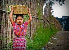 Guatemalan girl carrying basket full of bananas after school - photo by Jay Cassario