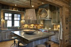 Located in the mountains of North Carolina, this kitchen uses cabinets made from aged gray barn wood to create the look and feel of an old cabin. The upper cabinets have chicken-wire inserts backed with a checked fabric that matches the curtains.
