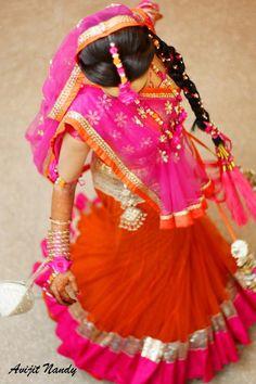 Indian wedding photography. Bridal photoshoot ideas. Candid photography. Pink and orange lehenga and dupatta. Bridal hairstyle. Flower inspired maang tikka.