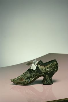 1740-1750 The piece shown here is a pair of women's shoes made with luxurious silk  damask. The latchets are tied with ribbons. This shoe is an excellent piece  that  shows the fashion at that time; with its a thick, curved Louis Heel which is associated with the age of Louis XIV, along with the upturned, pointed toe. 18th century women's shoes were one luxury accessory that symbolized the elegant and sophisticated Rococo culture.