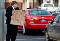 """CASEY PAGE/Gazette Staff    Forest Westwood, a freshman public relations student at Montana State University Billings, spent part of his evening standing on the corner of North 27th Street and Fourth Avenue North a sign that read """"Be Happy."""""""
