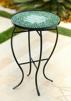A beautiful green mosaic graces the top of this outdoor iron accent table.