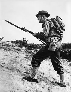 Anonymous USA World War II infantry soldier advancing across a rough terrain with rifle and bayonet at the ready. Military Photos, Military History, Ww2 Uniforms, Bataan, Military Diorama, United States Army, Korean War, World War One, Martial Arts