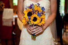 A bouquet of sunflowers and blue delphinium is perfect for the summertime bride!