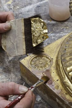 Re-gilding the base of one of the torcheres. ©NTPL/John Hammond