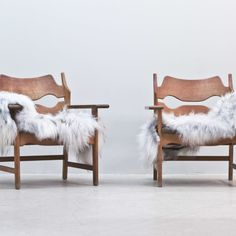 Pair of Danish armchairs in oak frame with original upholstery designed by Henning Kjaernulf. Covered in Icelandic sheepskin (removable). Please contact us for ideas of new upholstery if requested. Sold as a pair. Designer:Henning Kjaernulf. Year:1950s. Country:Denmark. Condition:Great vintage condition. Sheepskin are new. Dimensions: H: 75 cm W: 72 cm D: 54 cm