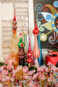 Glass Christmas tree finials displayed in vintage genie bottles. - Jennifer Perkins