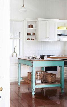 Passthrough window over sink with transom, turquoise island with white perimeter cabinets, open cabinets