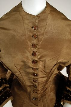 1856-58, watered silk tea gown, 2-piece toffee colored with darker trim on the sleeves and lower bodice edge, close up.