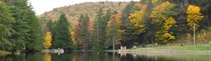 Fall leaves and evergreens covers the mountains that frame the lake at Raymond B. Winter State Park, Pennsylvania.