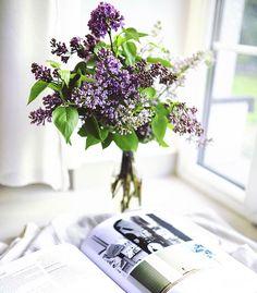 Quarto minimalista branco com cantinho de leitura decorado com flores de cor roxa
